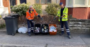 Rubbish collectors by boxes of recycling